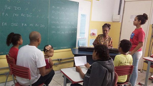 Voluntários conduzem aula de música para alunos da EMEF José Inocêncio Monteiro, em Tremembé (SP)